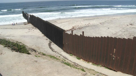 A family is seen playing on the beach next to the border wall in Tijuana Footage