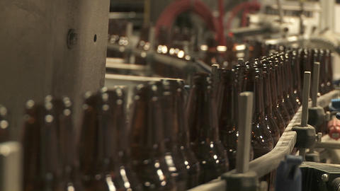 Bottles zip along a conveyor belt in a bottling plant Footage