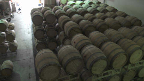 Pan across barrels of beer in a warehouse Stock Video Footage