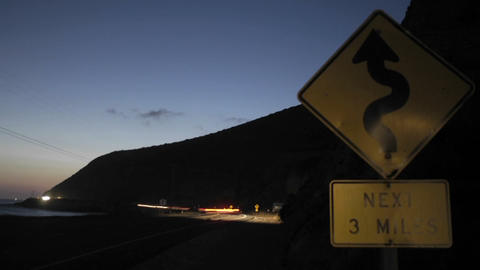 A time lapse shot of traffic at night passing a roadsign Stock Video Footage