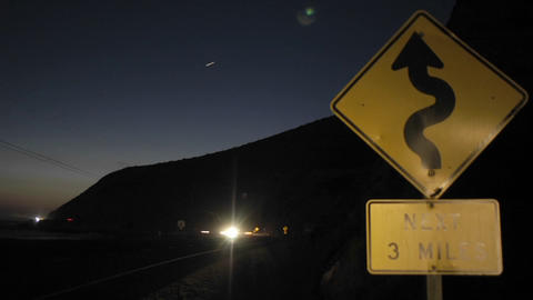 A time lapse shot of traffic at night passing a roadsign Footage