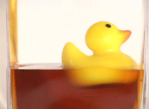 Oil fills up a clear container with a rubber duck floating on top Footage