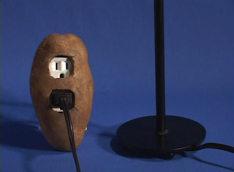 Tilt up from a potato to a light bulb which lights up,... Stock Video Footage