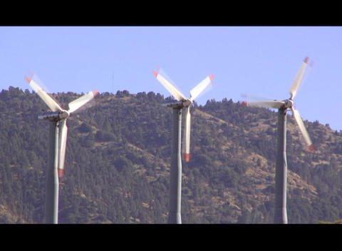 Three windmill blades rotate near a mountainside Stock Video Footage