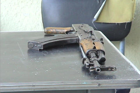 An M16 rifle sits on a table in an interrogation room Stock Video Footage