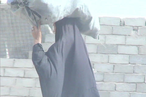 A veiled Muslim woman walks down a street in rural Iraq... Stock Video Footage