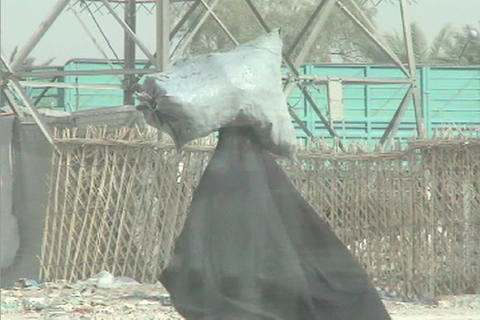 A veiled Muslim woman walks down a street in rural Iraq carrying a bag of goods on her head Footage