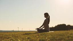 Japanese woman practising yoga in a city park at sunset, Tokyo, Japan Filmmaterial