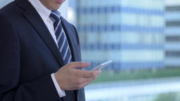 Young Japanese businessman with smartphone in a modern office Footage