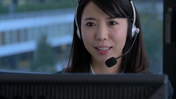 Young Japanese woman working at a call center in a modern office 이미지