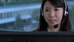 Young Japanese woman working at a call center in a modern office Footage