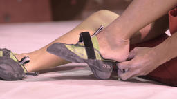 Japanese athlete putting shoes on before climbing a wall in a bouldering gym Footage