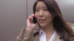 Slow motion footage of Japanese young woman talking on the phone while walking d Footage