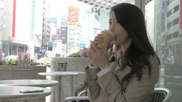 Japanese young woman having coffee in a cafe downtown Tokyo Footage