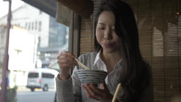 Slow motion footage of Japanese young woman eating at a traditional restaurant d Footage