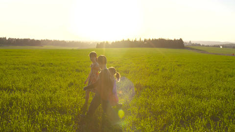 Three kids walking in a field during sunset Footage