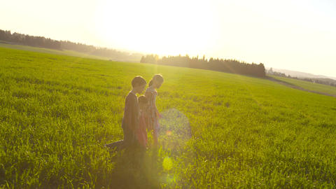 734 Three kids walking in a field during sunset Footage