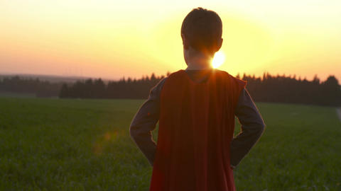 Boy with superhero cape standing in a green field during sunset Footage