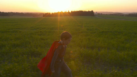 Boy with superhero cape running in a green field during sunset GIF