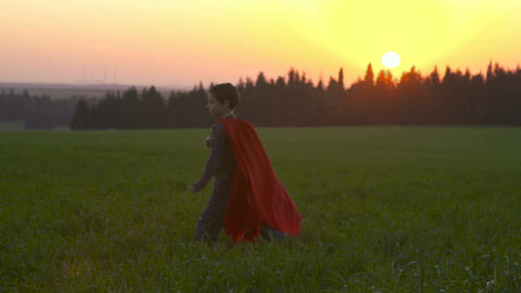 Boy with superhero cape running in a green field during sunset Footage