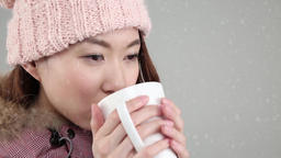 Young attractive Japanese woman in snowboard outfit drinking coffee under fallin Footage