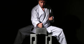Japanese karate athlete breaking tiles on black background Footage