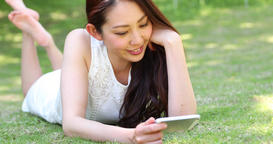 Attractive smiling young Japanese woman watching videos on her smartphone laying GIF 動畫