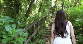 Attractive young Japanese woman walking in a green forest wearing a white dress Footage