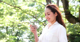 Attractive young Japanese woman in a white shirt watching video on her smartphon Bild
