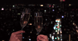 Japanese people hands toasting with Champagne, night cityscape in the background Footage