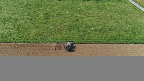 Aerial shot of donkeys pulling farming equipment フォト