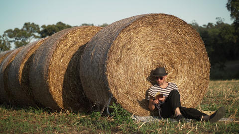 A young man chill in the field. A man in a stripe shirt and a black hat sitting Live Action