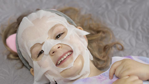 Teen girl applying moisturizing face mask. Child kid take care of skin with Live Action