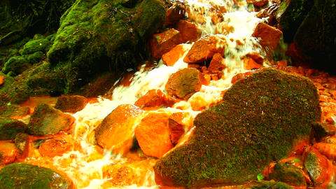 mooth stones in ferruginous water. Mineral water creek close-up. Clean water flow among red and Live Action
