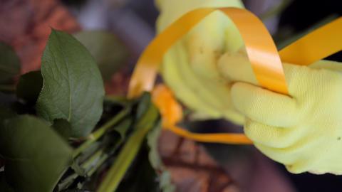 florist ties bouquet with ribbon and cuts edges in shop Acción en vivo