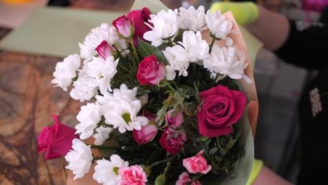 florist wraps gentle bouquet with colorful paper at table Acción en vivo