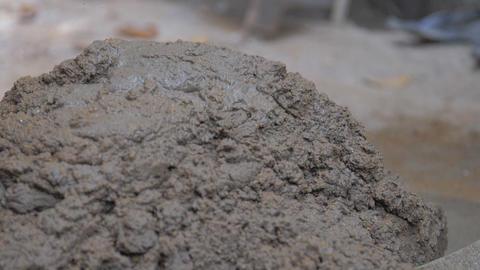 construction worker mixes wet grey cement holding shovel Live Action