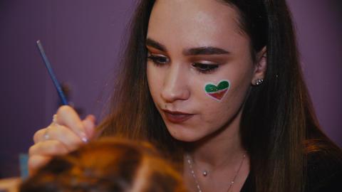 lady with shiny heart on cheek applies makeup on kid face Acción en vivo