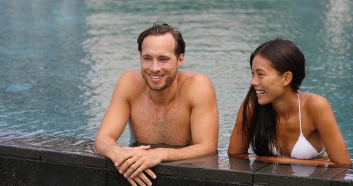 Couple relaxing together in swimming pool on vacation Acción en vivo