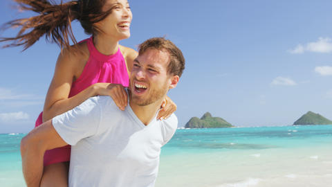 Beach couple having fun laughing on Hawaii holiday Live Action