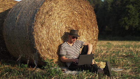 A young man works with laptop in the field. A man in a stripe tshirt and a black Acción en vivo