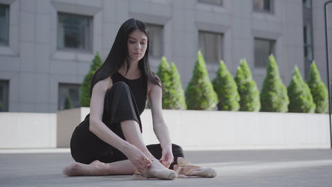 Portrait of serious charming woman tying up pointe shoes. Young confident Live Action