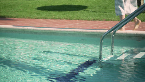 Barefoot girl in a striped dress is walking along the edge of the pool Acción en vivo