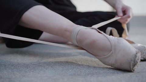 Close-up of female hands tying up laces on pointes on urban asphalt street Live Action
