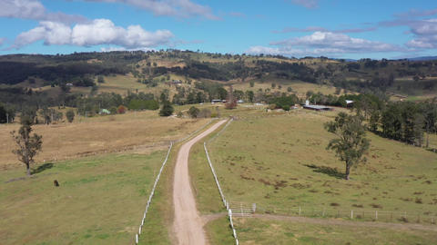 Aerial footage of a dirt road with white fence posts in green farming fields Live Action