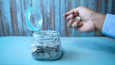 Man pouring coins into glass jar on table Live Action