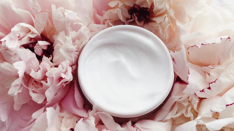 Organic face cream jar and peony flowers, clean moisturizer as skin care routine Live Action