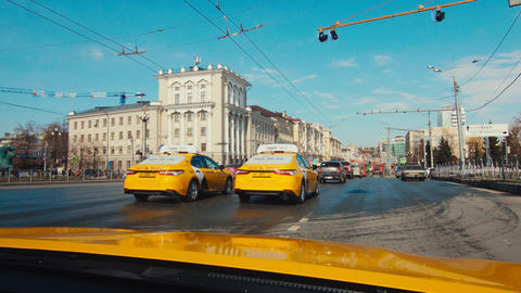 yellow Yandex taxi cabs drive along city street among cars Live Action