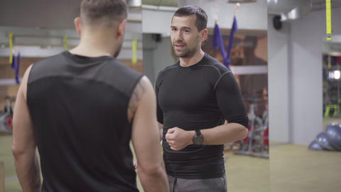 Portrait of confident personal trainer explaining workout program to young Live Action