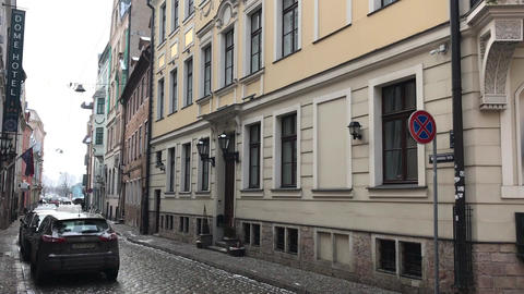 Riga, Latvia, A narrow city street with cars parked on the side of a building Live Action